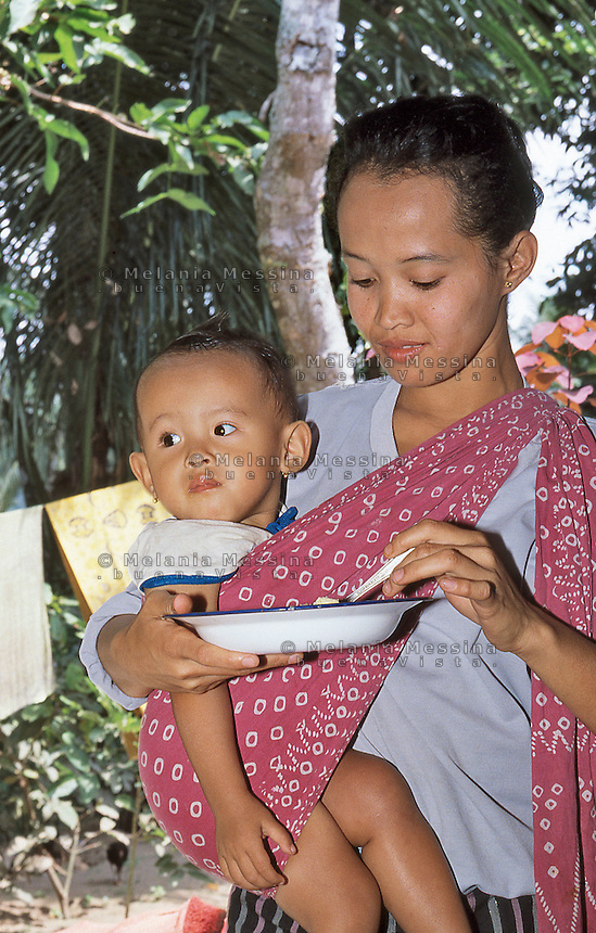 Indonesia, Java island, mother and child attending to posyando .