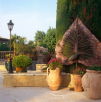 A copper sculpture of a leaf and a crane by artist Sara Bolzani stands amongst terracotta plant pots on a stone tiled terrace
