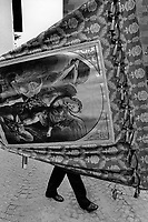 "Italy. South Tyrol. Tisens. Religious procession on August 15 for the Assumption. A man carries a painting from the New Testament depicting Michael leading God's armies against Satan's forces in the Book of Revelation, where during the war in heaven he defeats Satan. Roman Catholics refer to him as ""Saint Michael the Archangel"". The Assumption of the Virgin Mary into Heaven, often shortened to the Assumption, is also known as the Falling Asleep of the Blessed Virgin Mary, According to the beliefs of the Catholic Church was the bodily taking up of the Virgin Mary into Heaven at the end of her earthly life. The Assumption is a major feast day, commonly celebrated on August 15th. The feast is marked as a Holy Day of Obligation in the Roman Catholic Church. South Tyrol (German: Südtirol; Italian: Sudtirolo, also known by its alternative Italian name Alto Adige) is an autonomous province in northern Italy. 15.08.1999 © 1999 Didier Ruef"
