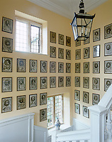 The walls of the staircase hall are lined with a collection of black and white prints of British historical figures
