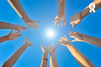 Group of hands raised on blue sky with the sun (Licence this image exclusively with Getty: http://www.gettyimages.com/detail/103544600 )