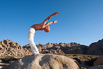 Man in exstatic yoga backbend outdoors in the desert.