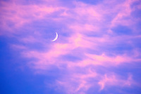 Crescent Moon Behind Cirrus Cloud in Evening