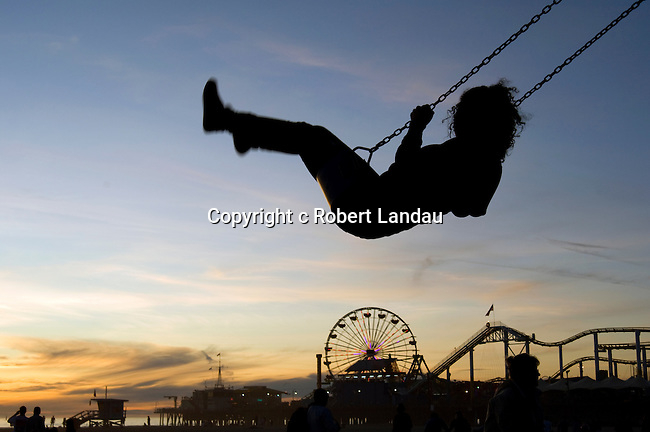 Girl playing on swing at playground at Santa Monica Beach
