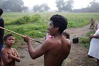 Viriunaveteri, Venezuela. Yanomami hunter showing his skill..The village of Viriunaveteri consists of 15 huts around a muddy square. It's situated in the Venezuelan Amazone several days by boat from the nearest town. This community on the banks of the Casiquiare is one of the few Yanomami villages that actually has some contact with the outside world. Most other tribes live deeper in the jungle.