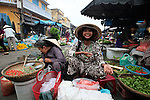 A woman smiles for a picture in the central market of Hoi An, Vietnam. April 22, 2012.