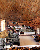 A vaulted brick ceiling arches over the living room where banquette sofas are upholstered in black and white fabric in harmony with a collection of photographs displayed along the wall behind