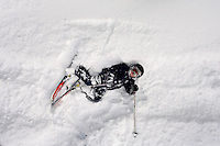 A young crashed skier lays in powder on a ski run at Showdown Ski Area on King's Hill in the Little Belt Mountains near Neihart, Montana, USA.