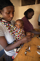 "Monica Waithira (24) and baby Ian Kimani (7 months), from the Korogocho slum, make key rings for the Italian fashion brand MAX&Co. in the Babadogo Community Centre, Nairobi, Kenya, on Monday, Jan. 12, 2009. Monica is a member of Bidii Shoe Makers, a team of 15 who create part of MAX&Co.'s ""ethical fashion"" range in Africa. The key-rings were made by Bidii Shoe Makers, a small group of 15 people who were contracted to create part of MAX&Co.'s ""ethical fashion"" range in Africa. The programme, in partnership with the ITC, is designed to reduce extreme poverty and empower women. Producing 30 - 50 key-rings per day the women can earn as much as $5 per day, much higher than the average wage for people in this part of Nairobi. The limited edition collection consists of one-of-a-kind handmade accessories such as shoulder-bags, bracelets, key-rings, belts and scarfs."