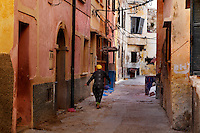 """View from behind of a woman walking in a narow street of the old city of the Portuguese Fortified city of Mazagan, El Jadida, Morocco. El Jadida, previously known as Mazagan (Portuguese: Mazag""""o), was seized in 1502 by the Portuguese, and they controlled this city until 1769.  Picture by Manuel Cohen"""