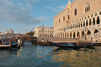 The Doge's Palace or Palazzo Ducale on the right, begun 1340 and built in Venetian Gothic style, with gondolas moored, and behind, the Biblioteca Nazionale Marciana, or National Library of St Mark's, built in Renaissance style in 1537-53 by Jacopo Sansovino, then extended by Vincenzo Scamozzi in 1588, on the Piazzetta San Marco, Venice, Italy. The palace has 2 arcades with 14th and 15th century capitals and sculptures, and a loggia above with a decorative brickwork facade. It was the residence of the Doge of Venice, the supreme authority of the former Republic of Venice, until the Napoleonic occupation in 1797, and is now a museum. The city of Venice is an archipelago of 117 small islands separated by canals and linked by bridges, in the Venetian Lagoon. The historical centre of Venice is listed as a UNESCO World Heritage Site. Picture by Manuel Cohen
