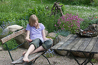 Mädchen sitzt im Garten und liest, neugierige Hühner gucken zu, Zwerghuhn, Zwerghühner, Idylle, Landidylle