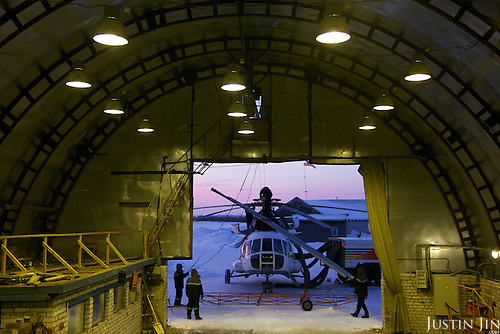 A helicopter is being repaired outside a hangar in Naryan-Mar. Flying is often the only mode of transport across the vast Arctic tundra, with thick snow in the winter that melts into marshland in summer.