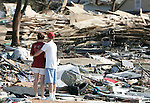 """Rachel and Cory Gregs, of Biloxi, Mississippi, take a moment to themselves as they stand in what used to be their apartment at the Quiet Water Apartments on Beach Blvd August 30, 2005.  Hurricane Katrina completely obliterated over 100 units of the Quiet Water apartments and St Charles Condiminiums with a reported 30 fatalities August 30, 2005.  """"There were more than 80 ifatalities n Harrison County"""" according to Mississippi Governor Haley Barbour."""