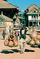 Man carrying heavy pots on shoulder hoist, Patan, Nepal
