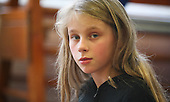 """Potrait of one of the girls in a drama group for 8-13s run by Yvonne Arnaud Theatre, rehearsing a production of """"Alice"""" in a school hall, Guildford, Surrey."""