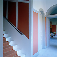 In the entrance hall walls are decorated with painted panels in orange, pink and grey