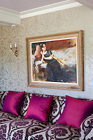 A gilt framed portrait hangs above a purple pattern sofa with vibrant fuchsia pink cushions.