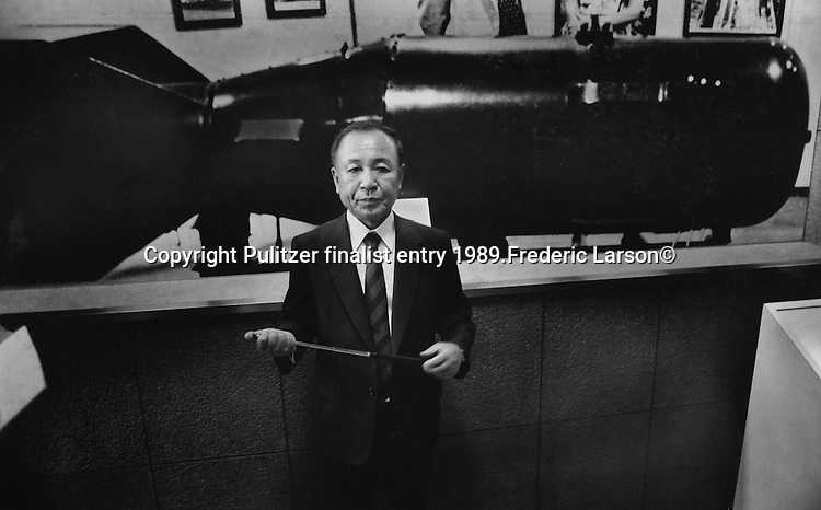 "Yoshitaka Kawamoto, Director of the Hiroshima Memorial Museum and a survivor of the bomb, stands in front of a full-scale model of the bomb, nicknamed ""Little Boy,"" which was dropped on Hiroshima. .Pulitzer finalist entry 1989 Frederic Larson©"
