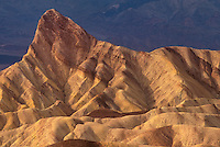 739650016 colored sandstone formations at zabriski point with manly beacon prominent in the scene in death valley national park californai