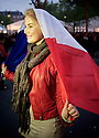 A smiling girl celebrates wrapped in a French flag.