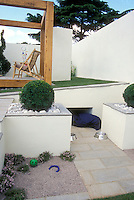 Backyard with pets in mind: Great problem solving idea to use sloped hillside cut to create dog house and water area and shower area of deck for pet washing in family outdoor space with stone patio.