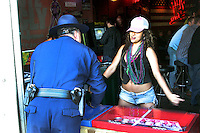 An unidentified girl gives a cop a little Mardi Gras jiggle as New Orleans celebrates the first Mardi Gras since Hurricane Katrina. (2006)