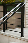 A sleek, black metal railing contrasts the light grey stone steps.