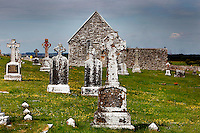 Low angle view of Gravestones and Temple Connor, 1010, by Cathal O'Conor, Clonmacnoise, County Offaly, Ireland, in the evening. Clonmacnoise was founded by St Ciaran, with the help of Diarmait Ui Cerbaill, Ireland's first Christian King. The site presents the largest collection of Early Christian graveslabs in Western Europe. Picture by Manuel Cohen