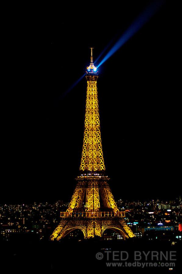 Eiffel Tower at night with illuminated beacon