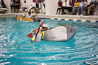 "Alex Penaranda, a senior, pilots his team's boat in the Brooklyn Technical High School Cardboard Boat Regatta in the school's pool in Brooklyn in New York on Friday, March 1, 2013. As part of Engineering Week the teams of students constructed boats made only of cardboard and duct tape. The team's assigned ""captain"" piloted their boat from one end of the pool to the other and back in a heat with other boats, hopefully without sinking. The surviving boats were timed and the winners received bragging rights with an award also going to the most spectacular sinking. (© Richard B. Levine)"