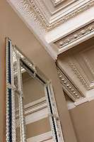 A Venetian mirror in the entrance hall echoes the ornate plasterwork of the apartment's coffered ceiling