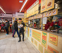 Customers pack the Papaya King store in Downtown Brooklyn in New York on Saturday, March 4, 2017 to gorge on 32 cent hot dogs. Started in 1932 the hot dog chain celebrated its 85th birthday with the discounted dogs!  (© Richard B. Levine)