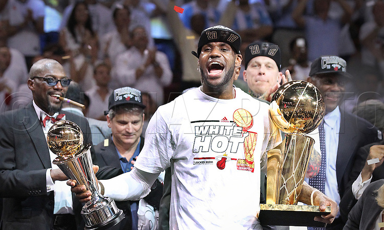 The Miami Heat's LeBron James celebrates with the MVP and championship trophy after defeating the Spurs in Game 7 of the NBA Finals between the Miami Heat and the San Antonio Spurs at the AmericanAirlines Arena on Thursday, June 20, 2013.