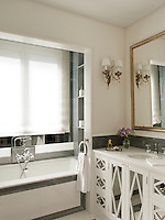 A modern white and grey bathroom with a washbasin set in a cupboard unit with a mirrored front. A bath is set to one side in a recess.