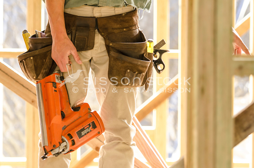 Builder with tool belt on and holding a nail gun, timber framing behind, New Zealand - stock photo, canvas, fine art print