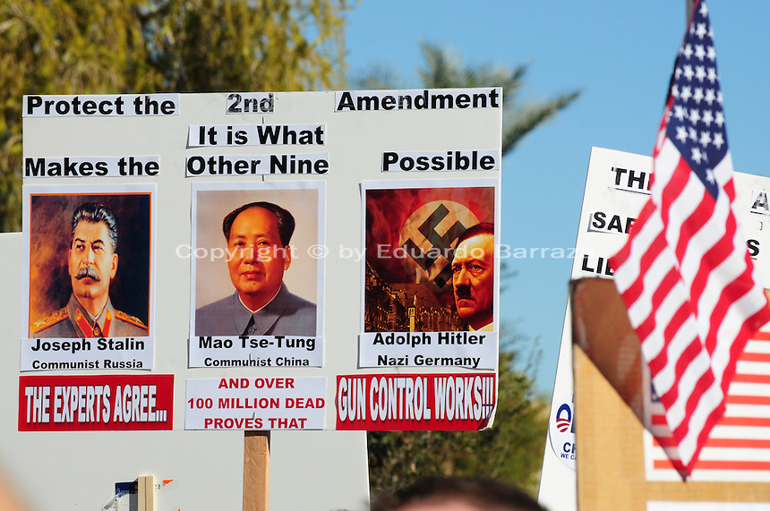 """Phoenix, Arizona. January 19, 2013 - A sign in favor of protecting the Second Amendment includes photos of Joseph Stalin, Mao T'se-tung and Adolf Hitler. As President Barack Obama proposed new gun regulations last week, gun owners demonstrated against it with national """"Guns Across America"""" rallies to defend the Second Amendment. Dozens showed up at the Arizona State Capitol, many of them carrying weapons. Photo by Eduardo Barraza © 2013"""