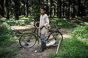 An estate worker poses with his bicycle at the Kerasaan palm plantation in Sumatra, Indonesia. Photo: Sanjit Das/Panos