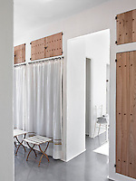 The bright dressing room has built-in wardrobes covered with white curtains and rustic wooden cupboard doors