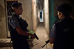 Pacifying Police officers Carla Bon, left, and D&eacute;borah Rocha, right, during patrol in Complexo do Caju, Rio de Janeiro, Brazil, on Friday May 10, 2013.<br /> <br /> In the early hours of Sunday, March 3, 2013, about 1,400 Brazilian security forces occupied 13 communities during a joint public security operation to install a Pacifying Police Unit (UPP) in two Rio de Janeiro favelas, Complexo do Caju and Barreira do Vasco. Elite police units backed by armored military vehicles and helicopters invaded the neighborhood in an on-going policing program aimed to drive violent and heavily armed drug gangs out of Rio's poor communities, where the traffickers have ruled for decades. For the community of Caju, that is ADA (Amigos de Amigos) and CV (Comando Vermelho).