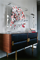 In the living room a plexiglass scuplture by Pleben is exhibited on a brass-trimmed 60s sideboard by Roger Landault