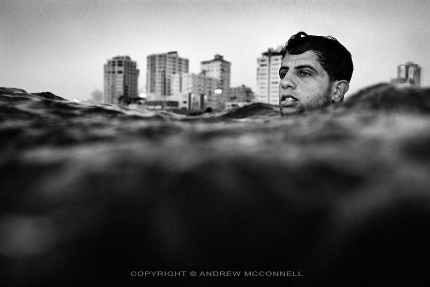 24 year-old Hatem Krazem paddles out from Gaza City, Gaza Strip. The sea off Gaza suffers problems with pollution as 60 million litres of raw and partially treated sewage are pumped into it every day.
