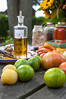 An outdoor harvest table set up for a meal under the trees with with whole heirloom tomatoes, olive oil, garlic, bottles of tomato sauce and sunflowers,