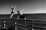 Teenagers diving and jumping off a railing into the waters of Miami Beach, Florida.