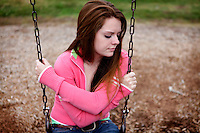 Kara sits on the swings at the Fairgrounds Park playground after school in Troy, Mo.