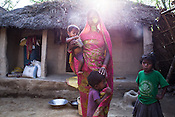 28 year old Asha Devi seen with her daughters - 11 month old Sharda, Rukmini (centre) and 4 year old Radha in the courtyard of their house in Saptari, Nepal. <br /> Asha Devi got married when she was 14. She got pregnant after 6 months of her marriage. Her first child survived for 6 days, she woke up next to a dead baby. She was pregnant two months later. Asha Devi's 2nd daughter survived for 9 months and later died due to prolonged fever. 3 months after her daughter died, Asha was pregnant again and within w months, she had spontaneous abortion. She was pregnant with Radha Kumari mandal who was acutely malnourished. Radha was admitted when she was 36 months old on October, 20th 2013. MUAC - 110 mm, Weight - 7 kg, Height - 75 cm. Radha was discharged on Dec 6, 2013 - her MUAC at the time of discharge was 128mm, Weight 8.8kg and height- 75.5 cm. She consumed 100 sachets of RUTF and gained 5gm/day while on the programme. <br /> Rukmini, her second daughter was born a year after Radha was born. Rukmini was severely malnourished too. She was admitted on Feb 16th, 2014. Her MUAC was 119mm, weight - 11 kg, and height - 96 cm. Her third daughter Sharda is severely malnourished. Sharda is under RUTF.  <br /> Asha Devi is pregnant for the 7th time and is 6 months pregnant.