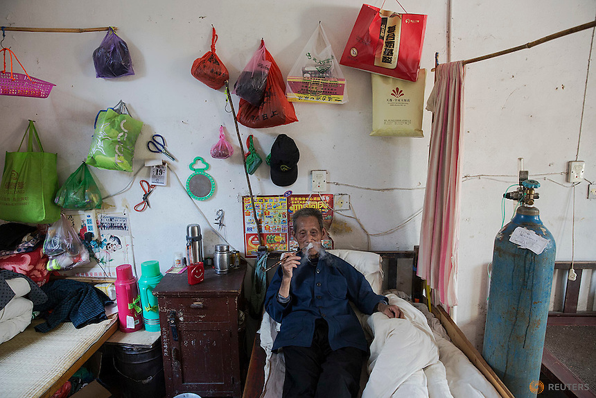 Wang Tianfang, a 87 year old pneumoconiosis patient smokes next to supply of oxygen supplement that he needs several hours pre day in his room at Yangjia Hospital in Wuji County, China's Zhejiang Province October 19, 2015. Wang Tianfang, a former miner who was diagnosed in 1973 with the disease caused by dust in lungs lives at Yangjia Hospital since two years ago. Although the hospital can't keep high standards since the mine company that built it went broke in 2001 and the medical institution became private, some of patients remain there because of its former reputation but also low price of service and more relaxed, friendly relationship between patients and staff.  REUTERS/Damir Sagolj