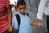 Jesus Haghighi, 7, holds his parent's hands, Yokayra Fernandez-Haghighi , left, and Saeid Haghighi, right, as they walk to school in Fordham Heights, The Bronx, NY on September 11, 2013.
