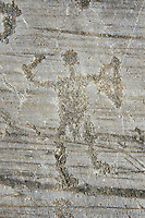 Petroglyph, rock carving, of a warrior with a sword and a round shield. Carved by the ancient Camuni people in the iron age between 1000-1600 BC. Rock no 24,  Foppi di Nadro, Riserva Naturale Incisioni Rupestri di Ceto, Cimbergo e Paspardo, Capo di Ponti, Valcamonica (Val Camonica), Lombardy plain, Italy