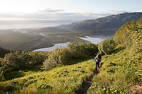 Stephanie Haynes hiking on the Alpine Ridge trail in Kachemak Bay State Park, near Homer, Alaska. Grewingk River drains the Grewingk Glacier lake into Kachemak Bay in the valley below.